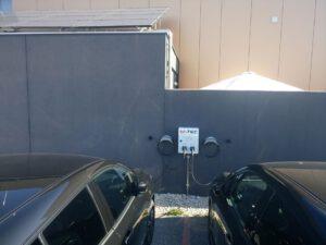 Ladestation für 2 E-Autos mit Photovoltaikanlage im Hintergrund