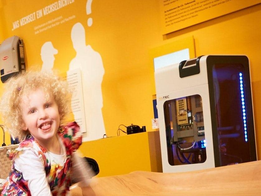 lachendes Kind vor einer M-TEC Wärmepumpe